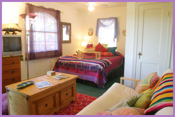 Mango Moon cabin is warm and inviting with a comfortable featherbed, kitchen and tree top deck where you can relax in a hammock while watching a full moon rise over the hillside swimming pool and fountain.